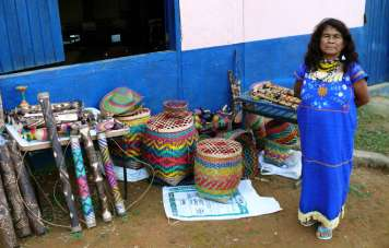 The caciques (chieftains) wife offers handcrafts